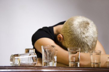 Young girl short blonde hair sick from alcohol laying on table