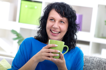 beutiful young woman sitting at her home drinking coffe, smiling