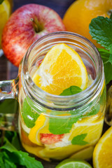 Mug delicious refreshing drink of mix fruits with mint on wooden