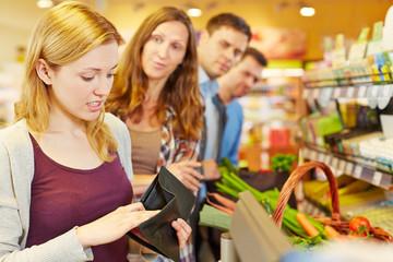 Frau an Kasse im Supermarkt sucht Geld