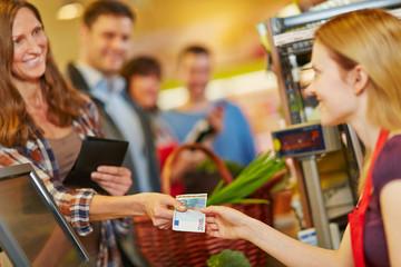 Frau zahlt mit Euroschein an Kasse im Supermarkt