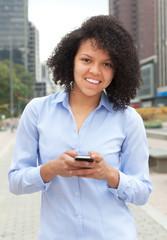 Frau aus Südamerika mit Handy schaut zur Kamera
