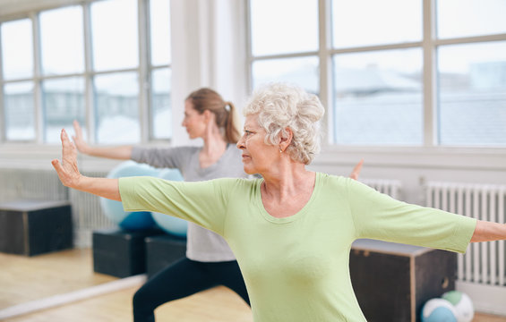 Two women doing yoga workout at gym