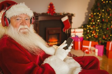 Smiling santa listening music with his smartphone