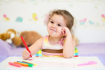 Little girl paints in nursery at home