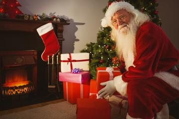 Smiling santa delivering gifts at christmas eve