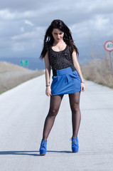 Woman in a blue skirt and black stockings on the open road
