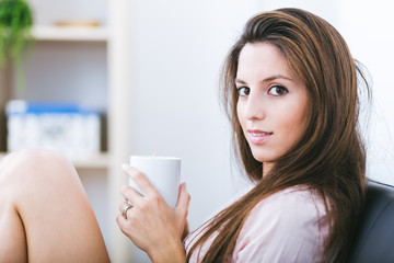 Smiling young woman on sofa with a cup of coffee at home