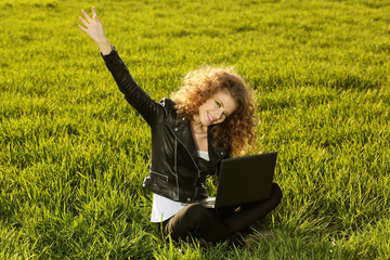 Beautiful lady with her laptop on grass