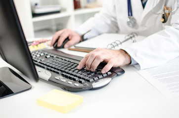 Doctor typing on a computer keyboard