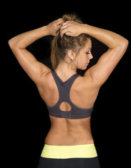woman in black sports bra from back look hands in hair