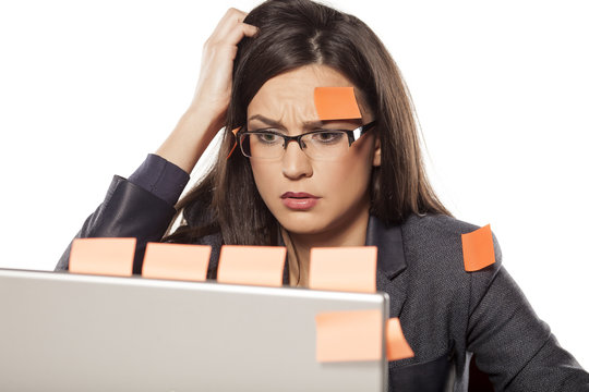 confused young businesswoman with stickers on her and her laptop