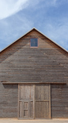 A wooden farm shed and blue sky