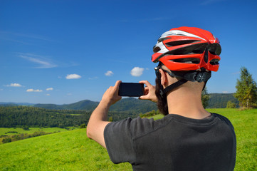 Cyclist taking pictures with smart phone.