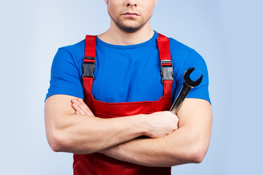 Serious young mechanic in red overall on blue background.