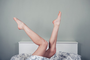 Woman lying in bed with legs raised