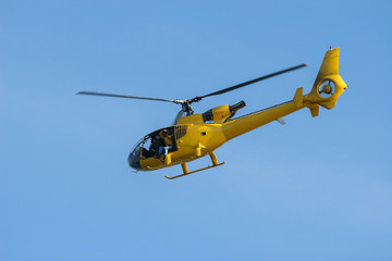 Small yellow private Helicopter in blue Sky