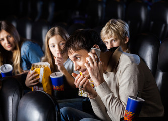 Angry Family Looking At Man Using Mobilephone In Theater