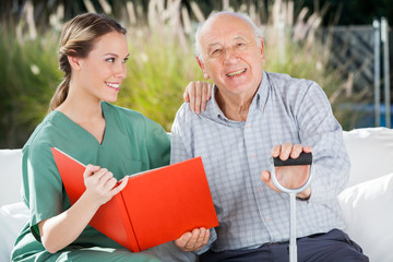 Happy Senior Man Sitting By Female Nurse Holding Book