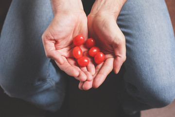 Man with handful of tomatoes