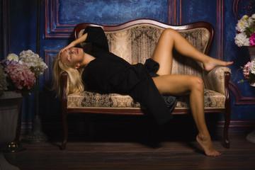 Sexy girl in a black coat in the dark room