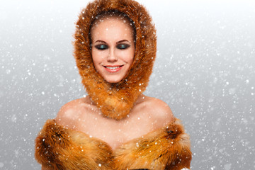 portrait of a girl in a fur hat on a background of snowflakes