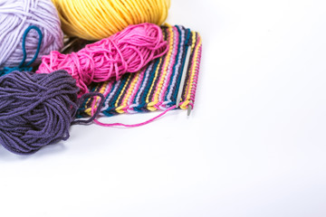 some ball of wool with a striped piece of knitting