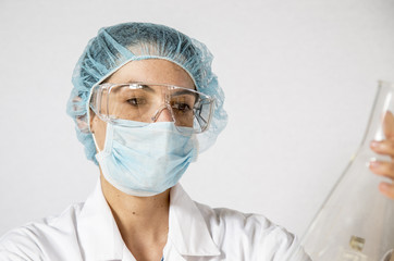 Female lab researcher in protective wear holding glass with chem