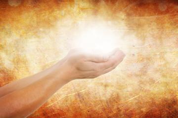 Hände halten strahlendes Licht