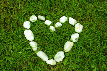 Heart of stones on grass