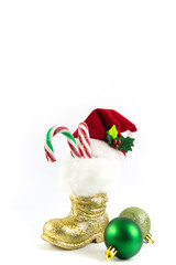 Santas golden boot and red hat with Christmas balls isolated