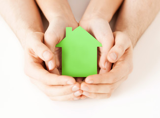 Wall Mural - man and woman hands with green paper house