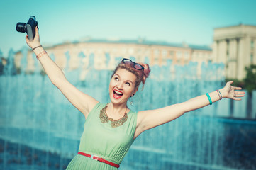 Beautiful happy girl in vintage clothing with retro camera