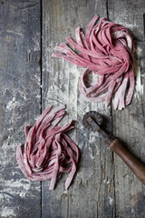 fresh tagliatelle with beetroot on rustic table with flour