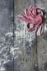 homemade pasta tagliatelle with beetroot on table with flour