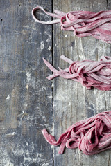fresh homemade pasta tagliatelle with beetroot on wooden table