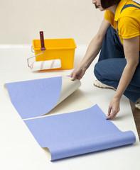 Woman unrolling wallpaper