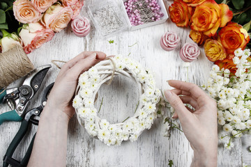 Florist making wicker wreath decorated with tiny daisies