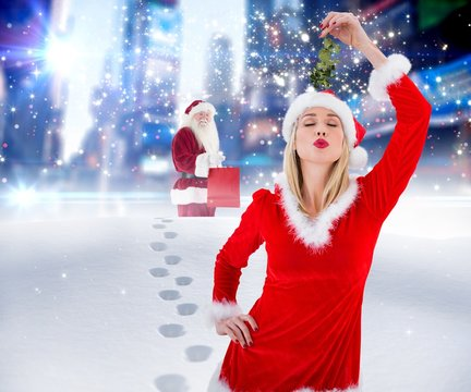 Composite image of festive blonde holding some mistletoe