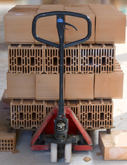 Hand pallet truck with bricks poroton on construction site