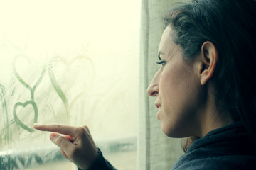 beautiful 35 year old woman stands in front of the window
