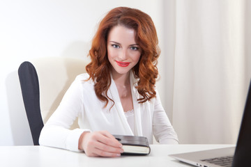 business lady in the white shirt sitting at table with laptop