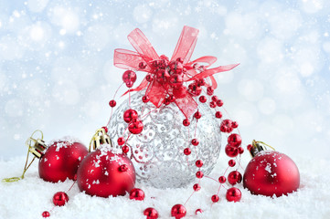 Christmas red and silver balls on snow on festive background