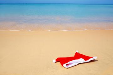 santa hats laying on beach sand
