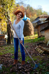 Farmer lady raking, cleaning the garden