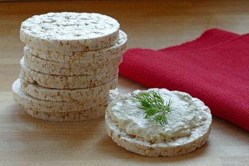 rice cakes, one with cream cheese and herbs on wood, red napkin
