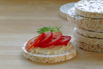 stack of of rice cakes, one with tomatoes on a wooden board,