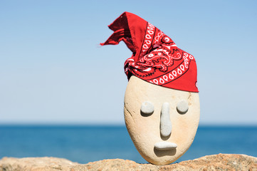 Symbol of stone head  with a patterned red bandana