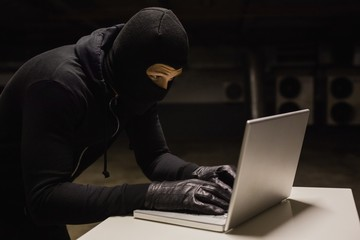 Fototapeta Robber at desk hacking a laptop