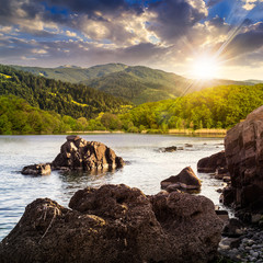 lake shore with stones near forest on mountain at sunset